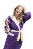 Blondes haooy Mädchen in trinkendem Champagner des Bademantels Stockfoto