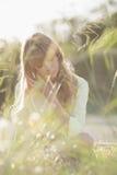 Blondes Hippie-Mädchen, das auf dem Gras sitzt Stockfotos