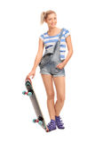 Blondes Hippie-Mädchen, das mit einem Skateboard aufwirft Lizenzfreies Stockfoto