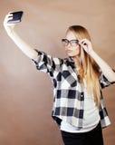 Blondes Hippie-Mädchen der Junge recht, das selfie auf warmem braunem Hintergrund, Lebensstilleutekonzept macht Lizenzfreie Stockfotografie