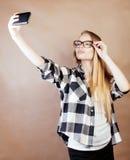 Blondes Hippie-Mädchen der Junge recht, das selfie auf warmem braunem Hintergrund, Lebensstilleutekonzept macht Stockfoto