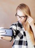 Blondes Hippie-Mädchen der Junge recht, das selfie auf warmem braunem Hintergrund, Lebensstilleutekonzept macht Lizenzfreie Stockfotos