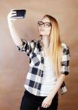 Blondes Hippie-Mädchen der Junge recht, das selfie auf warmem braunem Hintergrund, Lebensstilleutekonzept macht Lizenzfreie Stockbilder