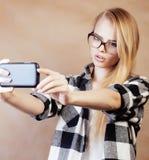 Blondes Hippie-Mädchen der Junge recht, das selfie auf warmem braunem Hintergrund, Lebensstilleutekonzept macht Lizenzfreies Stockfoto