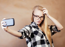 Blondes Hippie-Mädchen der Junge recht, das selfie auf warmem braunem Hintergrund, Lebensstilleutekonzept macht Stockfotos