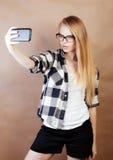 Blondes Hippie-Mädchen der Junge recht, das selfie auf warmem braunem Hintergrund, Lebensstilleutekonzept macht Stockbild