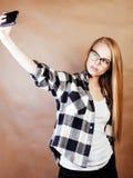 Blondes Hippie-Mädchen der Junge recht, das selfie auf warmer Braunrückseite macht Lizenzfreie Stockbilder