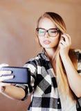 Blondes Hippie-Mädchen der Junge recht, das selfie auf warmer Braunrückseite macht Stockfotografie