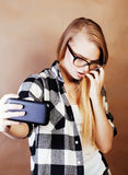 Blondes Hippie-Mädchen der Junge recht, das selfie auf warmer Braunrückseite macht Stockfotos