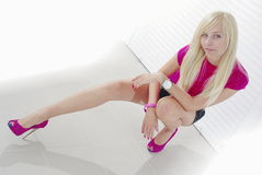Blondes Hocken auf Weiß Stockfoto