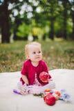 Blondes Jähriges der wenig Ethnie des Babys kaukasischen von der Geburt sitzt auf einem Plaid auf grünem Gras im Park und hält in Stockfotos