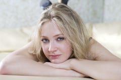 blondes jugendlich Mädchen, das auf Bett liegt Lizenzfreies Stockfoto