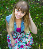 Blondes jugendlich Mädchen der Schönheit mit den großen Augen, die auf Gras sitzen Stockbilder