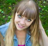 Blondes jugendlich Mädchen der Schönheit mit den großen Augen, die auf Gras sitzen Stockbild