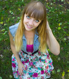 Blondes jugendlich Mädchen der Schönheit mit den großen Augen, die auf Gras sitzen Stockfotografie