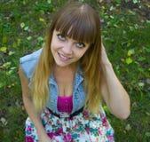Blondes jugendlich Mädchen der Schönheit mit den großen Augen, die auf Gras sitzen Lizenzfreie Stockbilder