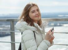 Blondes jugendlich Mädchen des jungen entzückenden Studenten, das mit Smartphone auf der Aussichtsplattform mit Blick auf den bew Stockfotografie