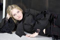 Blondes jugendlich Mädchen mit dem langen Haar, das auf Fußboden liegt Lizenzfreie Stockfotografie