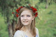 Blondes jugendlich Mädchen mit einem Kranz von Mohnblumen und von Gänseblümchen auf Kopf Stockbilder