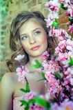 Blondes jugendlich Mädchen nahe einem blühenden Baum Lizenzfreies Stockfoto