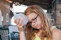 Blondes jugendliches kaukasisches Mädchen setzt Eis zum Kopf Lizenzfreie Stockfotografie