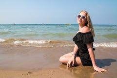 Blondes Jugendlichmädchen auf dem Strand nahe Meer Stockfotos