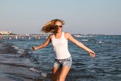 Blondes Jugendlichmädchen auf dem Strand nahe Meer Lizenzfreies Stockbild