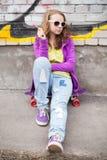 Blondes Jugendlichmädchen mit Lutscher, vertikales städtisches portra im Freien Stockbild