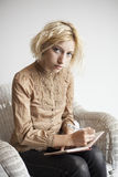 Blondes junge Frauen-Schreiben in ihrer Zeitschrift Lizenzfreies Stockfoto