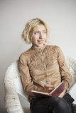 Blondes junge Frauen-Schreiben in ihrer Zeitschrift Stockbild