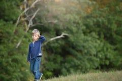 Blondes Jungengehen allein und traurig im Wald Lizenzfreies Stockfoto