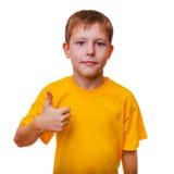 Blondes Jungenkind im gelben Hemd, halten Daumen-oben, Stockbilder
