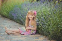 Blondes junges Baby haben etwas Spaß während der Sommerferienfeiertage Modeartsitzung nah an grünem Frühling lavander aufwerfend Lizenzfreie Stockfotografie