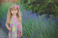 Blondes junges Baby haben etwas Spaß während der Sommerferienfeiertage Modeartsitzung nah an grünem Frühling lavander aufwerfend Lizenzfreies Stockfoto
