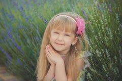 Blondes junges Baby haben etwas Spaß während der Sommerferienfeiertage Modeartsitzung nah an grünem Frühling lavander aufwerfend Lizenzfreie Stockbilder