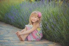 Blondes junges Baby haben etwas Spaß während der Sommerferienfeiertage Modeartsitzung nah an grünem Frühling lavander aufwerfend Stockfotos