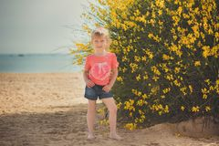 Blondes junges Baby haben etwas Spaß während der Sommerferienfeiertage Modeartsitzung nah an wildem Gelb des grünen Frühlinges au Stockbilder