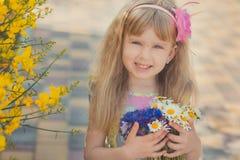 Blondes junges Baby haben etwas Spaß während der Sommerferienfeiertage Modeartsitzung nah an wildem Gelb des grünen Frühlinges au Lizenzfreie Stockfotografie