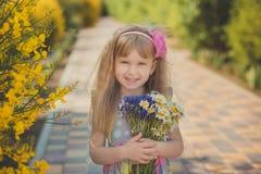Blondes junges Baby haben etwas Spaß während der Sommerferienfeiertage Modeartsitzung nah an wildem Gelb des grünen Frühlinges au Lizenzfreie Stockfotos