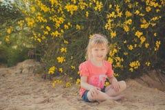 Blondes junges Baby haben etwas Spaß während der Sommerferienfeiertage Modeartsitzung nah an wildem Gelb des grünen Frühlinges au Lizenzfreies Stockfoto