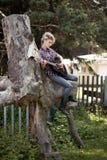 Blondes junges Bauernmädchen, das auf großem altem Stumpf sitzt Stockfotografie
