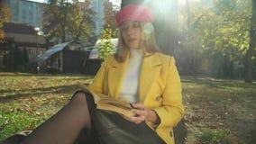 Blondes junges Mädchen, das ein Buch im Park liest stock video