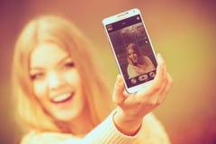 Blondes junges Mädchen, das ein selfie nimmt Stockbild