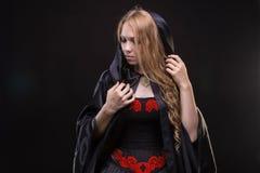 Blondes junges Mädchen im schwarzen Mantel Stockfotografie