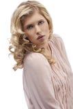 Blondes junges Mädchen mit dem lockigen Haar, das in Richtung blickt Lizenzfreie Stockbilder