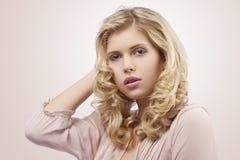 Blondes junges Mädchen mit dem Schauen des lockigen Haares Stockbild