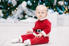 Blondes kaukasisches Babykind mit blauen Augen in rotem Santa Claus-Kostüm, das durch Baum des neuen Jahres sitzt Lizenzfreies Stockfoto