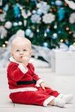 Blondes kaukasisches Babykind mit blauen Augen in rotem Santa Claus-Kostüm, das durch Baum des neuen Jahres sitzt Lizenzfreie Stockbilder