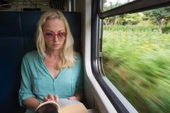 Blondes kaukasisches Frauenlesebuch auf Zug am Fenster Lizenzfreies Stockbild