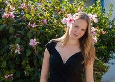 Blondes kaukasisches Frauenporträt, das mit Hibiscusblütenblume in ihrem Haar aufwirft Lizenzfreie Stockfotografie